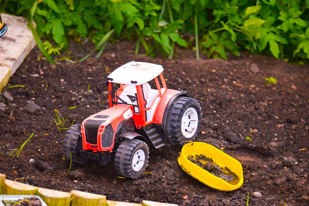 Playing in mud with toy tractor