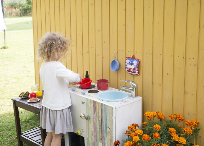 Child Playing in a mud kitchen